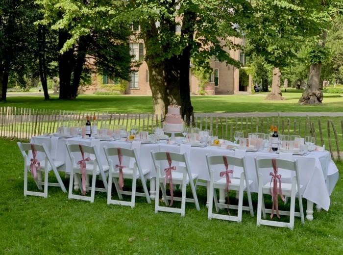 Een romantisch huwelijksdiner aan lange tafel in de tuin van de Hofboerderij te Kasteel keukenhof.